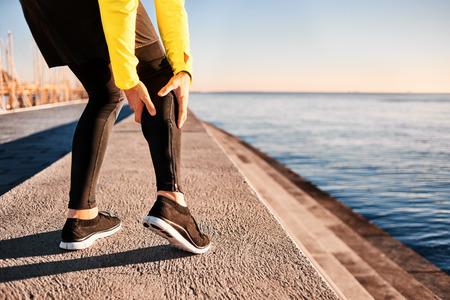 海の近くのビーチでジョギングをしながら捻挫後クラッチのふくらはぎの筋肉を実行している運動選手の筋肉の損傷。外の人間を実行しているスポ