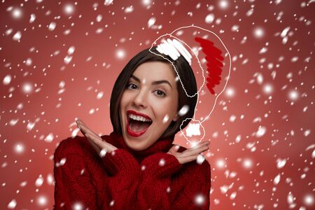 red lips: Mujer de Navidad. Modelo de la belleza en el sombrero de santa y un suéter rojo que se coloca alrededor de la nieve aislada. Retrato de la mujer de risa divertido sorprendida con la boca abierta. Las emociones verdaderas. Labios rojos. Maquillaje hermoso de vacaciones