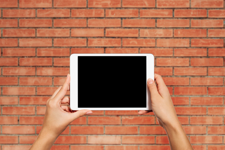 pc screen: Woman hands holding electronic tablet pc with blank screen. Isolated against texture wall background with copy space.