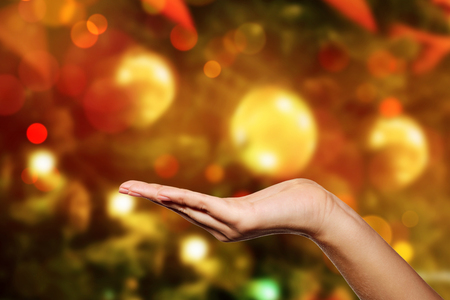Open a womans hand, palm up isolated against Christmas or New Year tree Stock Photo