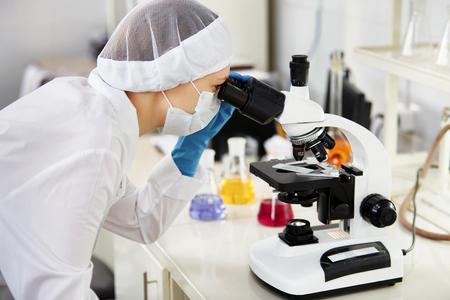 Jonge vrouw medisch onderzoeker kijken door microscop dia in de life science (forensische geneeskunde, microbiologie, biochemie, genetica, oncologie) laboratorium. Concept van de geneeskunde.
