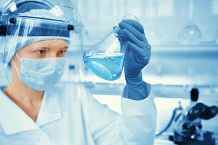 Closeup portrait female scientist holding conical tube with liquid solution, laboratory experiments, isolated lab background. Forensics, genetics, microbiology, biochemistry