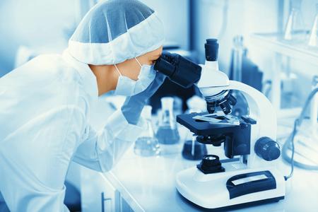 Investigador médico Mujer joven que mira a través de diapositivas microscop en la ciencia de la vida (la medicina forense, microbiología, bioquímica, genética, oncología) laboratorio. Concepto de la medicina.