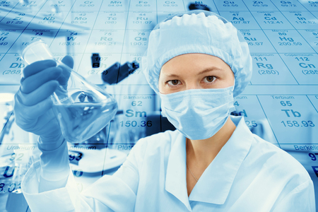 reagents: Science, chemistry, technology, biology and people concept - young female scientist mixing reagents from glass flasks and making test or research in clinical laboratory with chemical table background Stock Photo