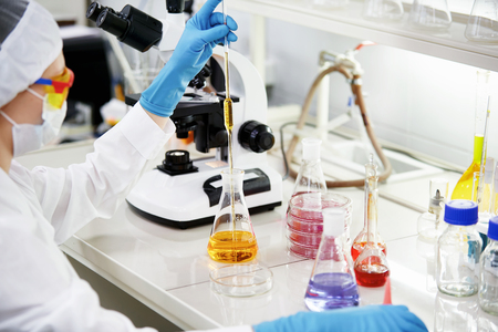 Science, chemistry, technology, biology and people concept - young female scientist mixing reagents from glass flasks and making test or research in clinical laboratory