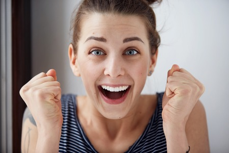 Surprised woman with hands up amazed or shocked by unexpected news holding close palms up and showing happy expression. Young adult woman on greybackground