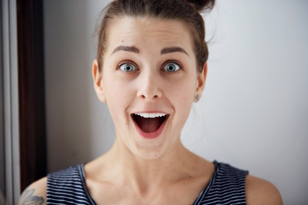 facial expression: Surprise astonished woman. Closeup portrait woman looking surprised in full disbelief  wide open mouth isolated grey wall background. Positive human emotion facial expression body language. Funny girl Stock Photo