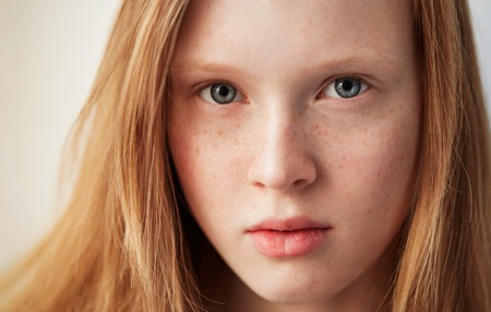 Young eyes girl beautiful redhead freckles woman face closeup portrait with healthy skin Stock Photo