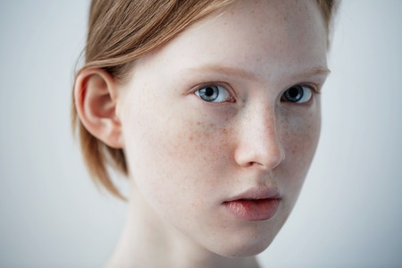 Beauty girl face Portrait. Beautiful model woman with freckles perfect fresh clean skin. Redhead female looking at camera. Youth and skin care concept. Isolated on background Banco de Imagens