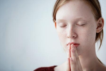 mujer orando: Bella pelirroja pecosa joven ruega muchacha adolescente. Cerca de retrato de una mujer de oración,