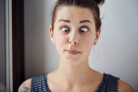 only 1 person: Young brunette woman looking cross-eyed. Closeup shot with wide angle and focus on the eyes. Harsh processing to emphasize the face structure. Human face expression body language reaction