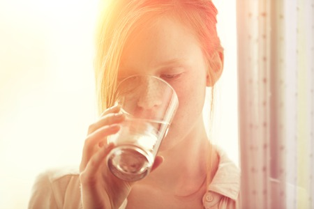 fresh water: Healthy redhead freckled girl young woman drinking a glass of water at home Stock Photo