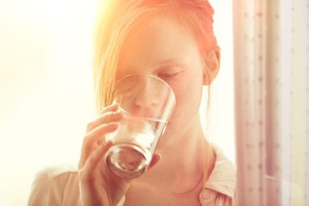 vasos de agua: Redhead sano pecosa joven beber un vaso de agua en el hogar Foto de archivo