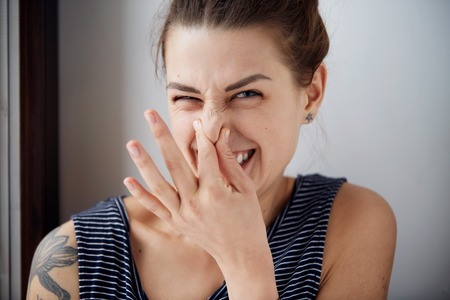 expression: Female gesture smells bad. Headshot woman pinches nose with fingers hands looks with disgust something stinks bad smell situation. Human face expression body language reaction