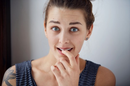 Embarrassed woman. Closeup portrait woman looking ashamed or shy in full disbelief isolated grey wall background. Positive human emotion facial expression body language. Funny girl