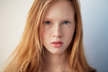 Young eyes girl beautiful redhead freckles woman face closeup portrait with healthy skin Foto de archivo