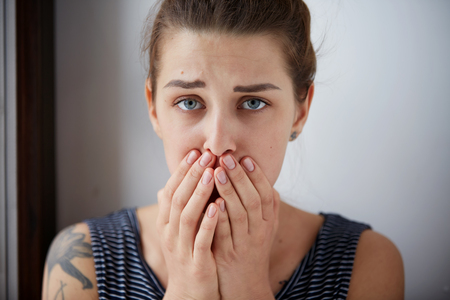 bad girl: Frustrated stressed young woman. Headshot unhappy overwhelmed girl having headache bad day keeps hands on face out isolated on wall background. Negative emotion face expression feelings perception