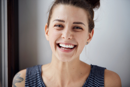 Beautiful model woman with freckles perfect fresh clean skin. Female looking at camera and laughing. Youth and skin care concept. Positive human emotion facial expression body language