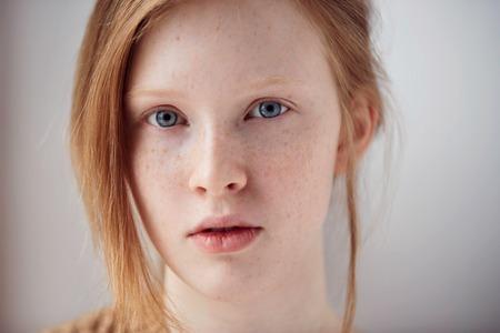 Portrait de belle fille pensive avec les cheveux rouges à la maison. rousse mignon et taches de rousseur visage de femme closeup portrait avec une peau saine.