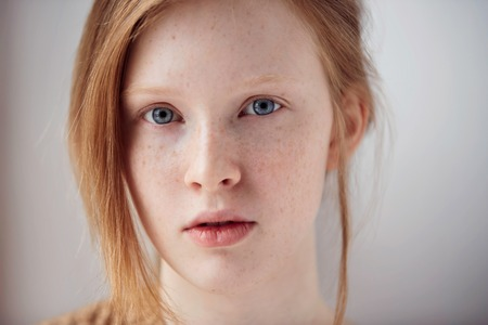 Portrait of beautiful pensive girl with red hair at home. Cute redhead and freckles woman face closeup portrait with healthy skin. Archivio Fotografico