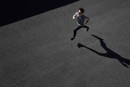 Man running on country road, healthy inspirational fitness lifestyle, sport motivation speed interval training. Runner jogging training and doing workout exercising power walking outdoors in city.