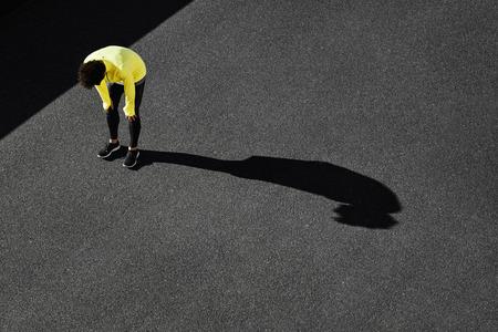Runner in het geel sportkleding rusten na het uitvoeren. Joggen man nemen van een pauze tijdens de training buiten in op zwart weg bovenaanzicht. Jonge blanke man fitness model na het werk uit.