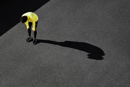Runner in yellow sportswear resting after running. Jogging man taking a break during training outdoors in on black road on top view. Young Caucasian male fitness model after work out. Stock Photo