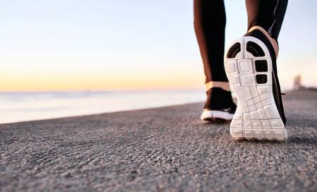 personas trotando: pies de atleta corredor ejecutan en primer plano cinta de correr en el zapato. Basculador del zapato de la aptitud en el fondo y el espacio abierto alrededor de él. Corredor de footing sesión de entrenamiento de ejercicio del poder caminar al aire libre en la ciudad. Foto de archivo