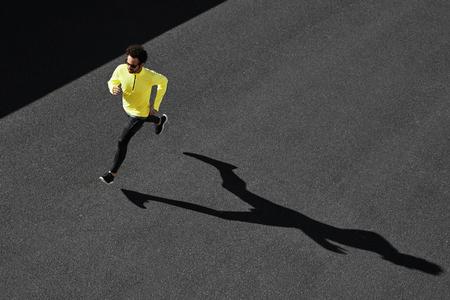 Running man sprinten voor succes op de run. Bovenaanzicht atleet runner training op hoge snelheid op asfalt. Gespierd fit sportmodel sprinter oefenen sprint in het geel sportkleding. Kaukasische fitness model Stockfoto
