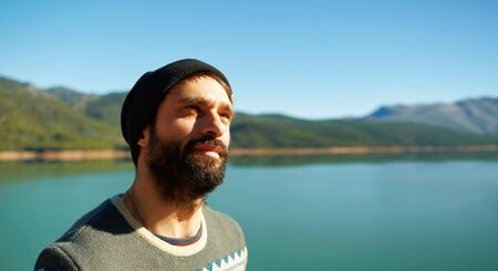 aucasian: Lake background. Hiking outdoors person looking at copy space to the side. Portrait of brutal strong multiracial ?aucasian model in Spain