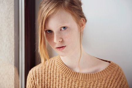 Portrait of beautiful pensive girl with red hair at home. Cute redhead and freckles woman face closeup portrait with healthy skin. Stockfoto