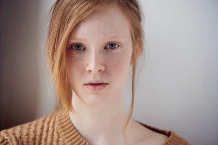 Portret pięknej dziewczyny z melancholijny rudych włosów w domu. Śliczne rude piegi i kobieta twarzy portret z bliska zdrowej skóry.