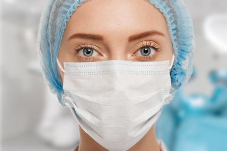 Close-up portrait of serious nurse or doctor in white mask. Looking confident and professional. Operation in the background