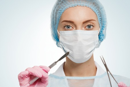scrub cap: Portrait of female surgeon wearing surgical scrubs, gloves and a scrub cap, holding a surgical scalpel in her hand