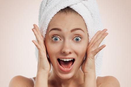 Überrascht aus der Dusche Frau schockiert. Schöne junge Frau Modell. Isoliert auf Hintergrund.