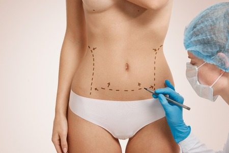 Beautiful woman with plastic surgery, depiction, plastic surgeon hands. Cosmetic surgery concept