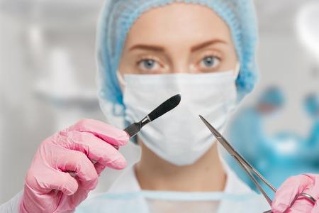 cirujano: Doctor de la mujer joven con el escalpelo y tijeras en la sala de cirugía, entre Foto de archivo