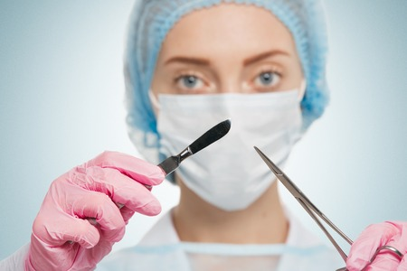 surgical scrubs: Portrait of female surgeon wearing surgical scrubs, gloves and a scrub cap, holding a surgical scalpel in her hand