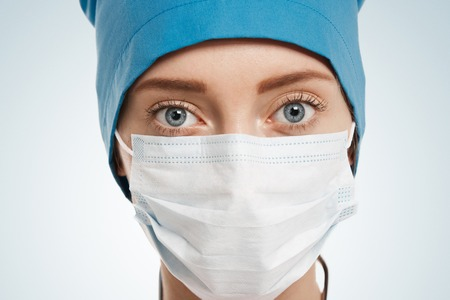 Close-up portrait of female surgeon isolated over background