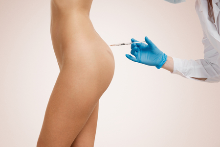 inyeccion: Inyección de Botox. Mujer joven y atractiva. Doctor en medicina y sombreros de bocetos, mientras que la mano haciendo una inyección en el cuerpo.