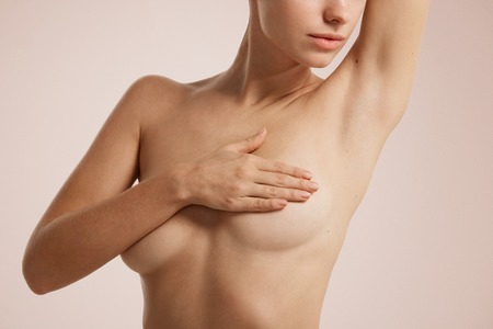 human cancer: Closeup cropped portrait young woman with breast pain touching chest colored isolated on background