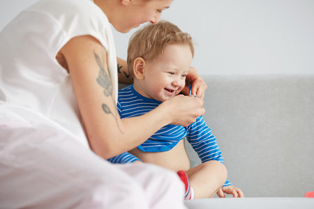 baby playing: Young mother with her one years old little son dressed in pajamas are relaxing and playing in the bedroom