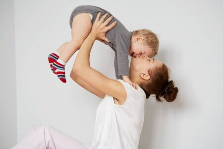 single family home: Young mother with her one years old little son dressed in pajamas are relaxing and playing in the bedroom