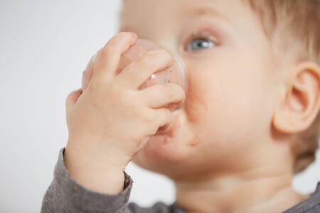 eating yogurt: Cute little boy eating yogurt. Stock Photo
