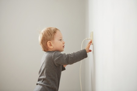 Curious little boy playing with electric plug. Reklamní fotografie - 53611192
