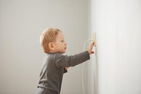 Cuus kleine jongen speelt met elektrische stekker. Stockfoto