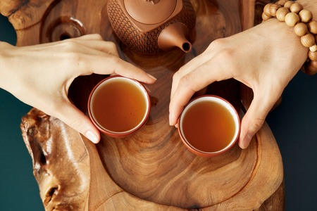 Top view tea set a wooden table for tea ceremony background. Man and woman holding a cup of tea