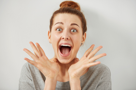 gossip: Surprise astonished woman. Closeup portrait woman looking surprised in full disbelief wide open mouth isolated grey wall background. Positive human emotion facial expression body language. Funny girl Stock Photo