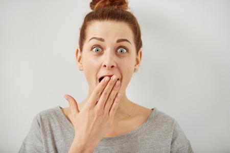 驚きびっくりした女性。見てみると口を大きく開けて完全不信でビックリ クローズ アップ肖像画の女性は、灰色の壁背景を隔離しました。肯定的な 写真素材