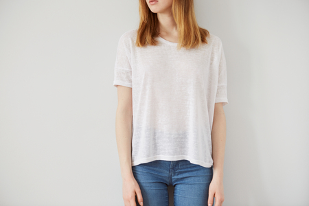 Young girl wearing blank wthite t-shirt. Wall background.